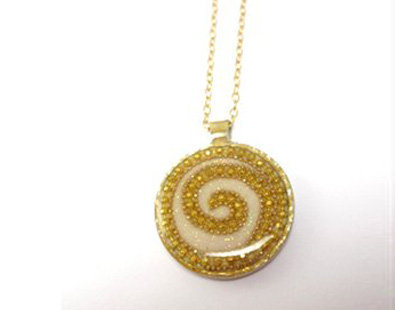 Gold dots spiral pendant on white background