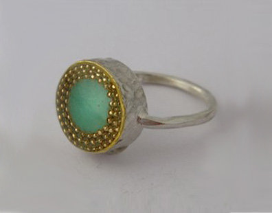 Green oval ring with gold dots contour