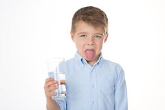 little boy making disgust face while holding glass of water