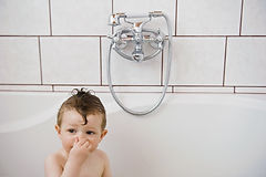 little boy in tub plugging his nose
