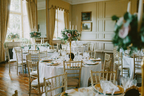 Tables dressed with ivory linen, and dressed with stunning brass candelabras, embellished with a full flower and foliage ring