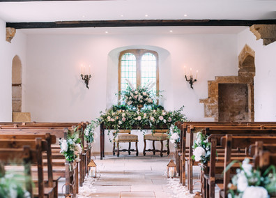 The beautiful aisle, adorned with fresh flowers and candles