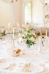 Low centerpieces encourage table talk among your guests. Intersperse a few tall candles for a declicate glow that still allows for easy conversation.