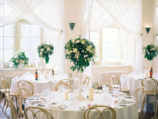 Candelabras give a romantic feel to your wedding breakfast; and add a touch of subtle elegance. They can be left as they are or surround the candlesticks with blooms for a fuller look. Pillar candles sat at the bottom, filling the table