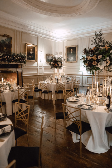 Winter wedding; rich and oppulent styling in the Salon. Tall gold column stands holding full flower designs. A modern minimalist setting takes on wintery elegance with white linens and popping dark accents. Simplistic flatware and a watercolor name card complete the modern look.