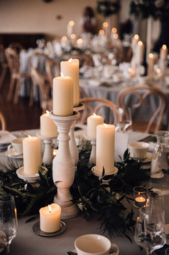 Low level centrepiece: Varying sized church pillar candles sat on white wooden candlesticks, sat on a bed of fresh Foliage