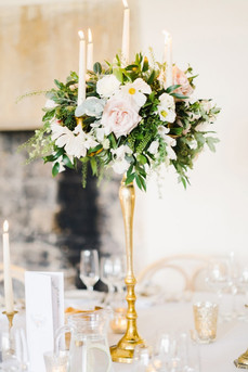 Stunning brass candelabras embellished with fresh blush toned flowers, surrounded with votives and candlesticks