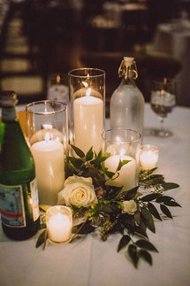 Flickering candles and warm hues set against a wall of greenery make this romantic tablescape inviting and cosy.