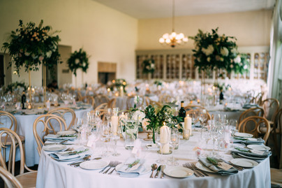 A mix of tall flower vases (held in column stands) and lower level urns. All designs surrounded with church pillar candles and votives   Albert Palmer Photographer