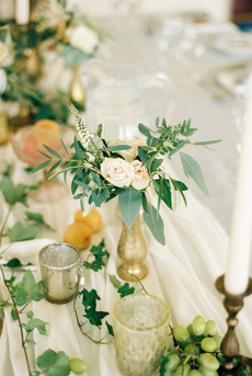 Add some fruit to your floral centerpieces for a feast-like feel. We love fruit spread throughout the table, whether it's placed neatly in small compotes or scattered about on its own! Silk table runners add a romantic feel to the setting