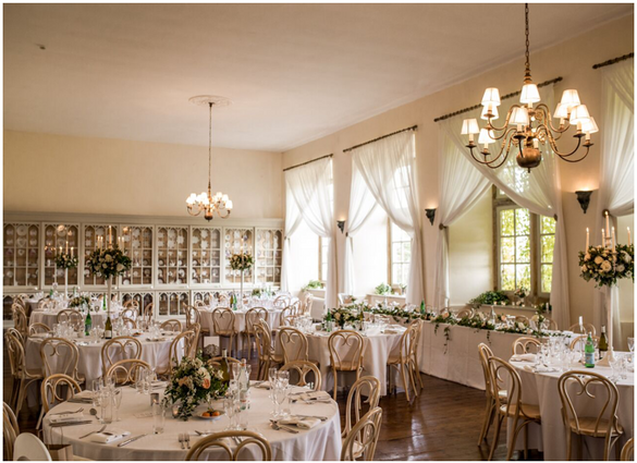 There's something especially great about mixing heights: it helps make the space look fuller and more interesting. Don't be afraid to do that with your table décor! Here, we're into how the tall white candelabras contrast with the low level urn designs