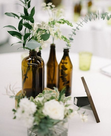 Vintage bottles holding stems: incorporating any sort of object, from antiques bottles to fine art, brings a new element to your wedding breakfast tables and makes the table feel not just pretty but interesting too!