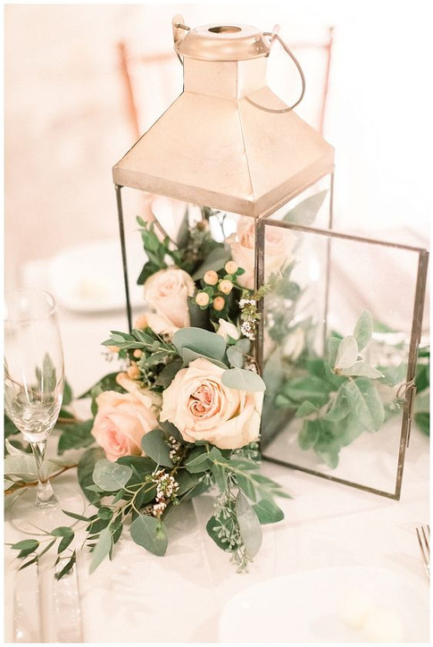 Style hurrciane lanterns with greenery and delicate florals for romantic centerpieces.