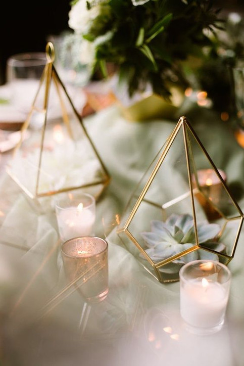 Succulents and candles in gold glass terrariums