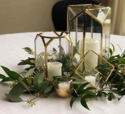 Play with shape and asymmetry on your tabletops. Here is a mix of our beautiful gold glass Geometric lanterns. The table top has been decorated with greenery