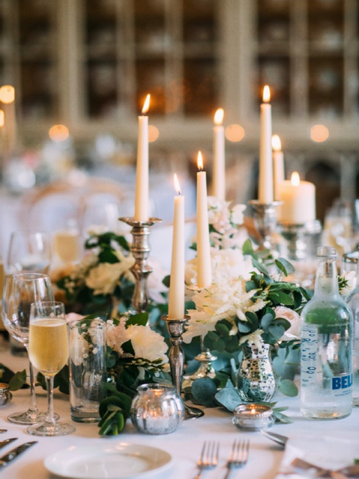 Pair mismatched candlesticks with fresh greenery and seasonal blooms for stunning centerpieces. We love this look for a chic Summer wedding.