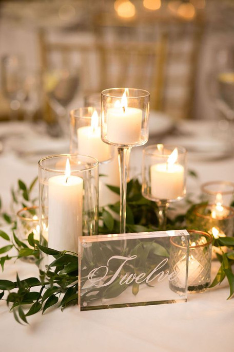 A scatter of stemmed votives and wider hurricane candles amid greenery for an effortless, elegant glow.