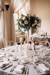 Close up of Tall white candelabras, embellished with Flowers and Foliage  Pillar candles sat at the bottom