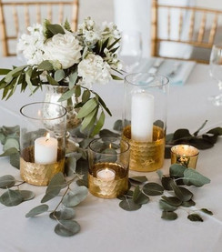 Delicate centrepiece: gold embellished glass lanterns, holding varying sized church pillar candles, sat on a bed of fresh Eucalyptus