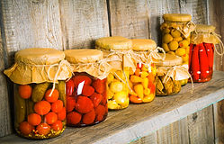 Preserved food in glass jars, on a woode