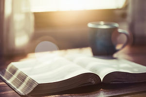 close up of open bible with a cup of cof