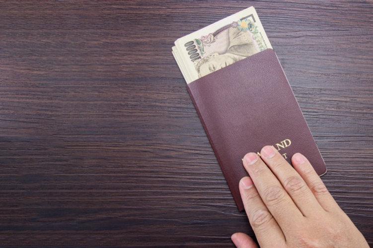 man-s-hand-holding-international-passpor