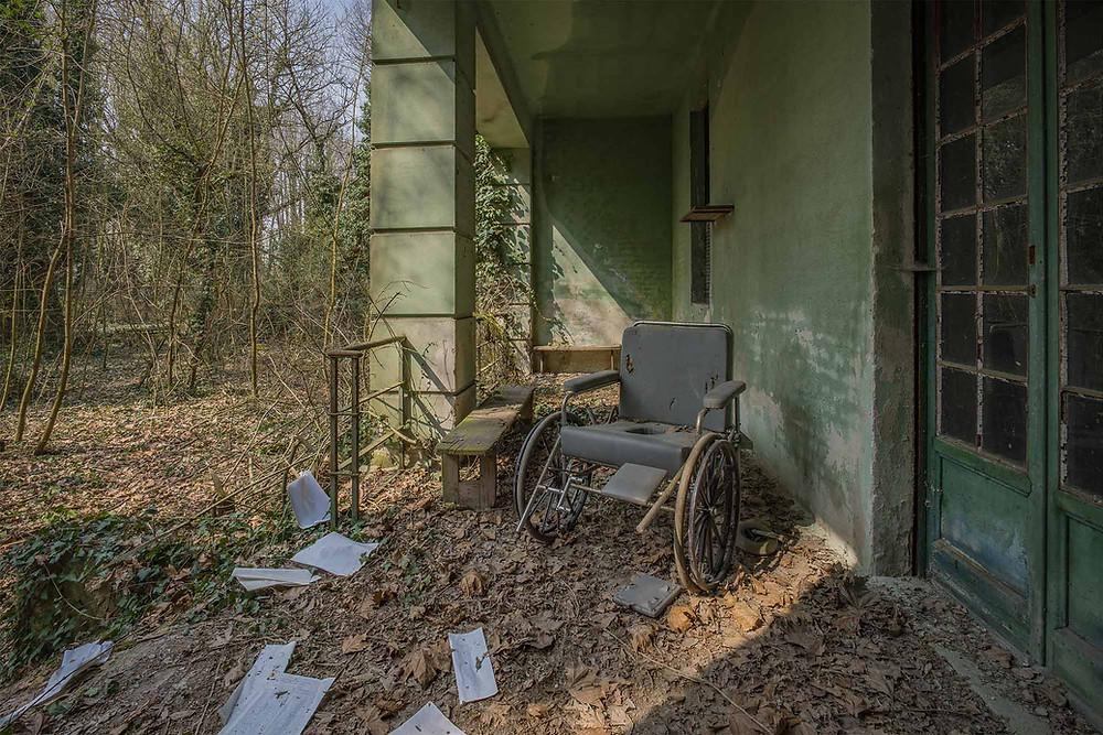 Kørestol udenfor på forladt psykiatrisk hospital