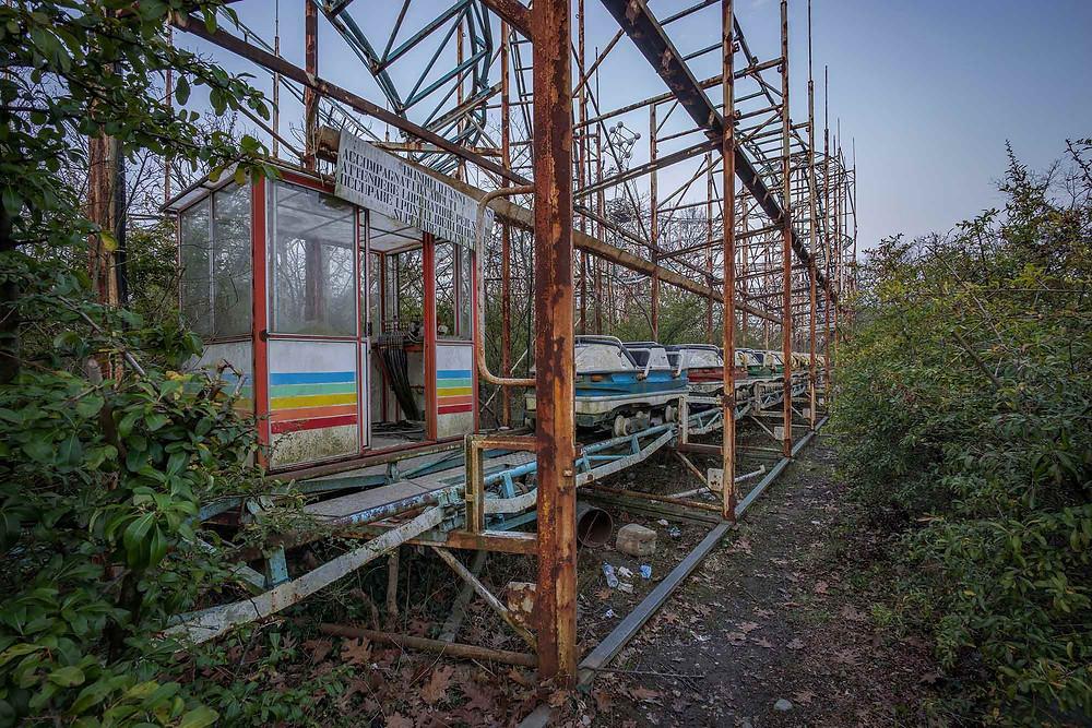 Rusty rollercoaster with carts in abandoned theme park