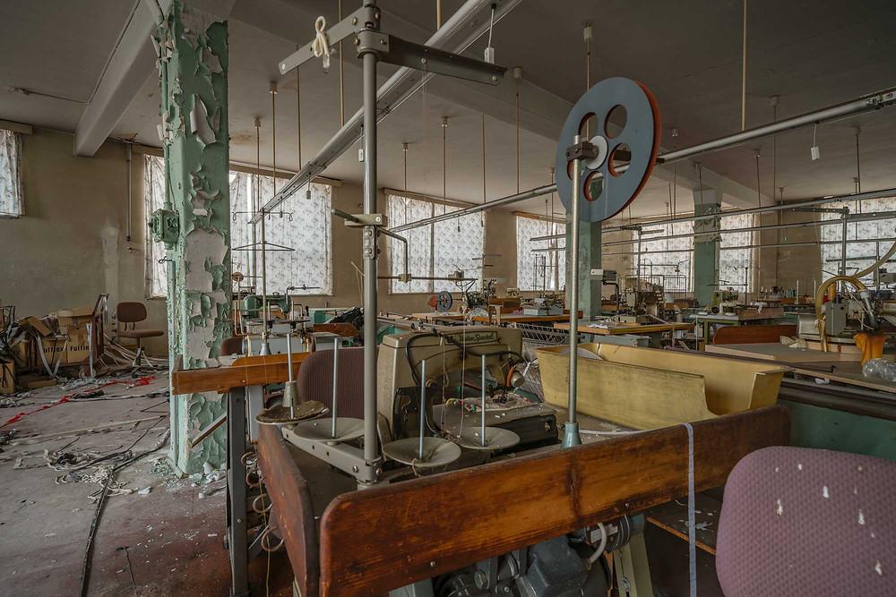 Symaskiner på forladt tøj fabrik