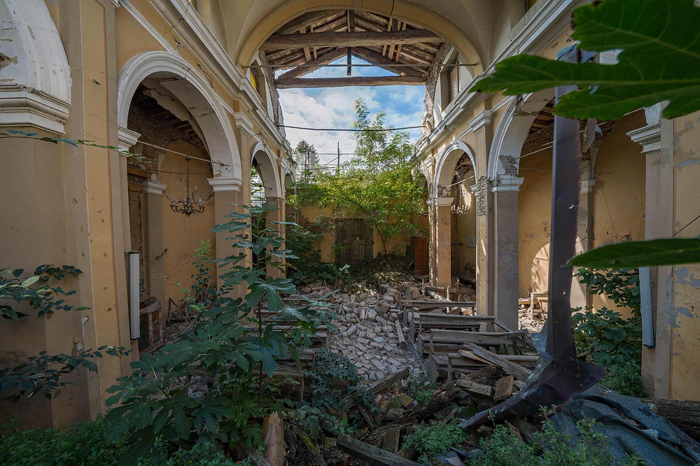 The chandeliers still hang in the abandoned church