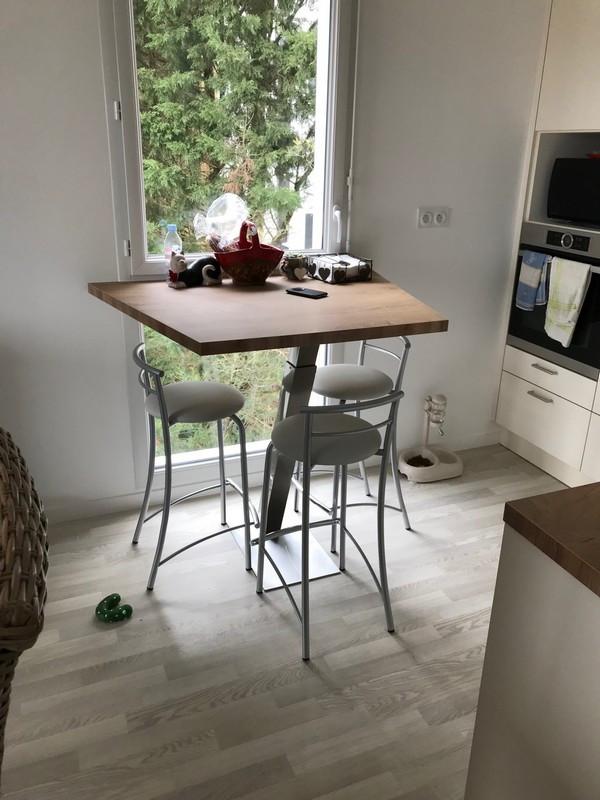 Aménagement d'un coin repas avec une table en forme de trapèze; avec pied oblique en inox