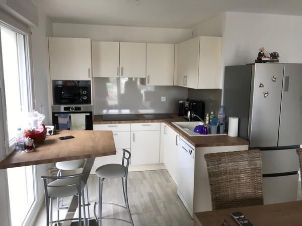 Aménagement d'une cuisine qui est très lumineuse, avec façades coloris Magonlia mat et poignées des placards sont en inox