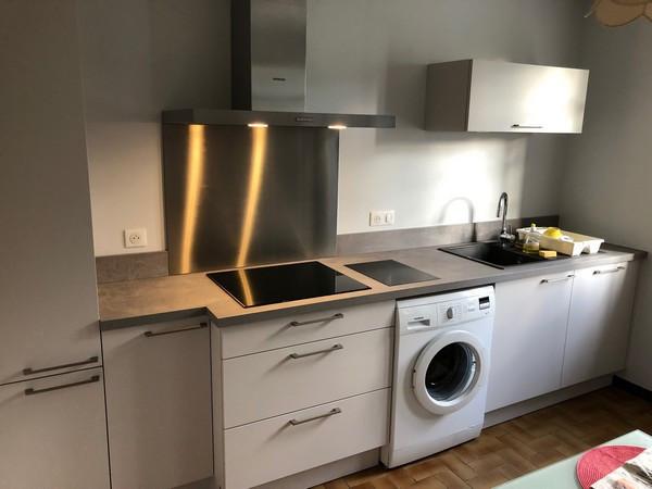 Aménagement d'une cuisine autour de la table existante. Il fallait aussi concevoir un espace pour le lave linge. Le plan de travail est posé dessus. Installation d'un petit meuble en hauteur avec des étagères.