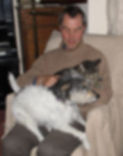 Man sitting with a dog and cat on his lap