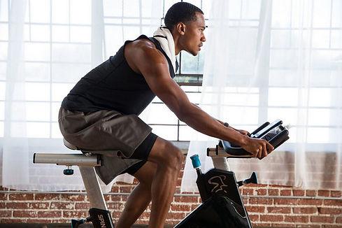 FITCITY Fitnes center v mestu | Gym & Spinning® Ljubljana| SPINNING® vadba je vadba na stacionarnem kolesu Spinner® pod vodstvom certificiranega SpinningⓇ inštruktorja. Kljub skupinski obliki, si vsak vadeči prilagodi intenzivnost glede na svojo fizično pripravljenost, starost in cilj. Tako lahko v isti skupini trenirajo začetnik, rekreativec in vrhunski športnik. Spinning® vadba je sestavljena iz lahkotnega ogrevanja, ki mu sledi intervalni del (klanci in spusti), zaključi pa se z ohlajanjem in raztezanjem. Osnova vadbe je merjenje srčnega utripa, ki pove, kako naporen in učinkovit je trening. Izmerite ga lahko sami, če se opremite z merilnikom, ki odčitava vaš srčni utrip. Novejša Spinning® kolesa imajo power meter, ki omogoča merjenje obremenitve in vložene moči ter razmerje med močjo, RPE, srčnim utripom in kadenco. Primerna je za vsakogar, ki želi fizično in mentalno napredovati, saj nas uči, da doseganje naših ciljev zahteva trud.