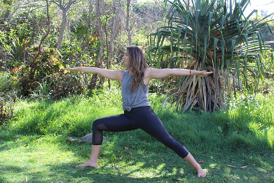 woman in warrior 2 yoga post in the jungle