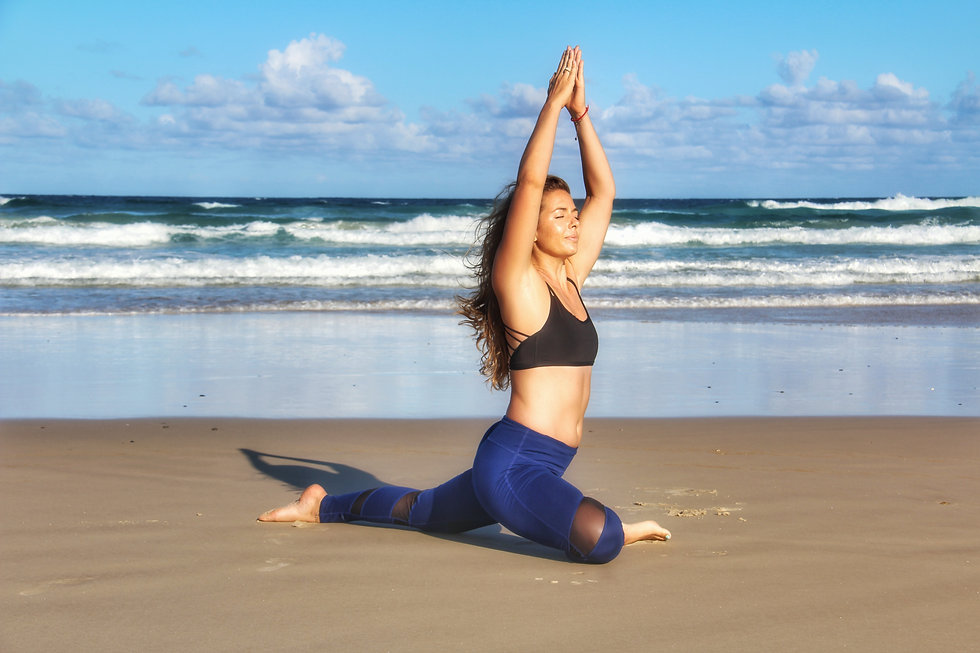 woman inyoga clothes in yoga pose on the sand at the beach with waves rolling in underneath a blue sky
