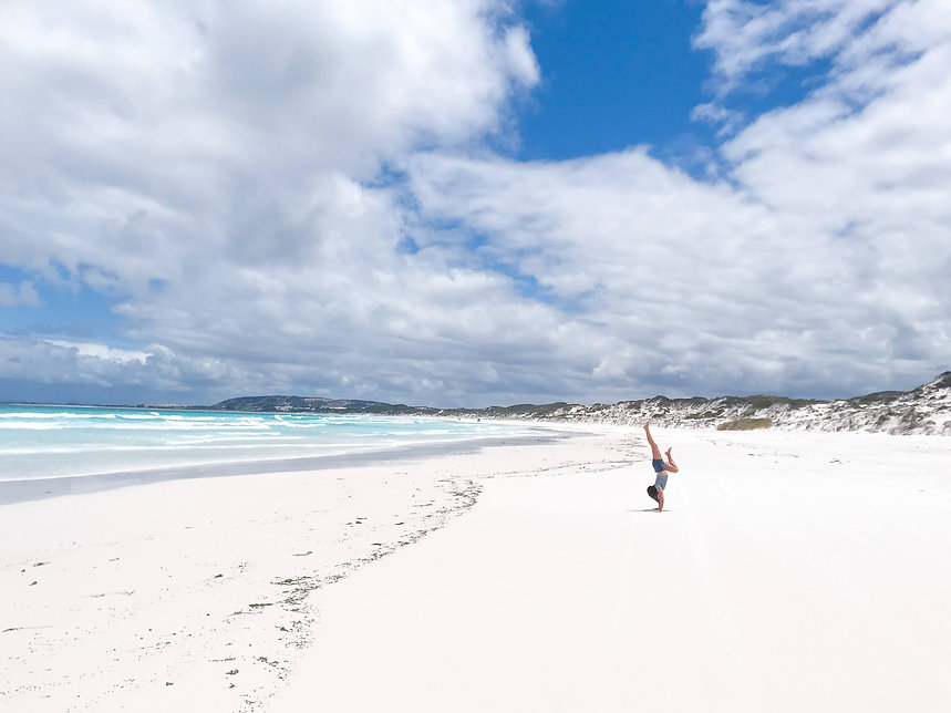 woman doing handstand on white sand at the beach with turquoise ocean and sand dunes behind her