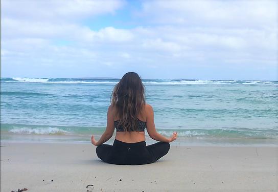 woman sitting at the beach meditating