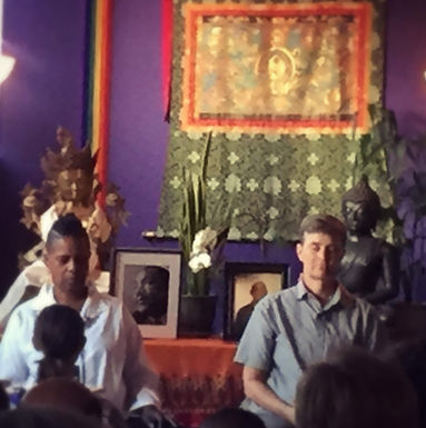 two people meditating, one black and one white, in front of purple wall with a Tibetan wall hanging