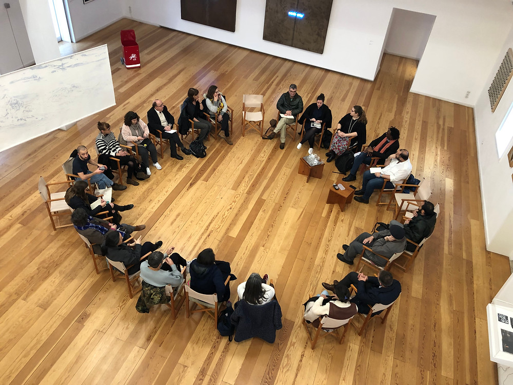 Aerial photo of people sitting in a circle during a talk.
