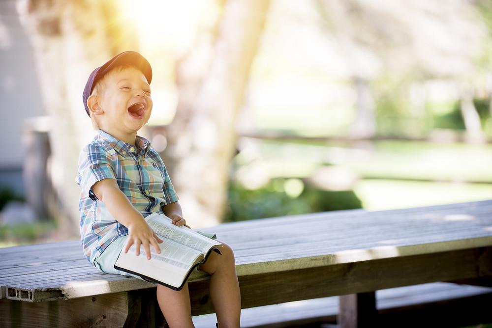Um menino com um livro no colo, numa rizada gostosa. O menino aparenta muita felicidade.