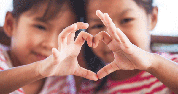 Two cute asian girls making heart shape with hands together