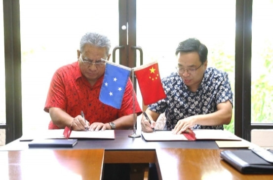 Dr. Taulung and Ambassador Huang signing their names on behalf of the FSM  and Chinese Governments respectively