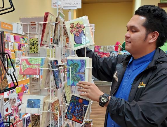 Shane Cruz arranges Monica Baza's cards rack in PayLess Supermarkets in Oka, Tamuning.