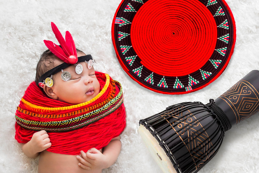 An African American baby with Kenyan beaded disc ornament, a feather head-dress, a djembe drum and a traditional African basket