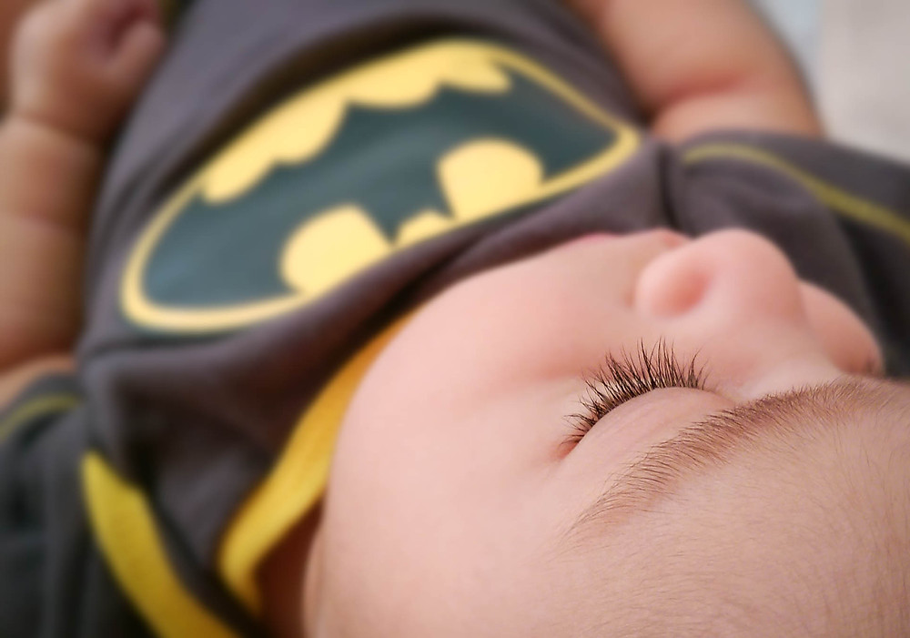 Long eyelashes of a sleeping baby in a batman onesie