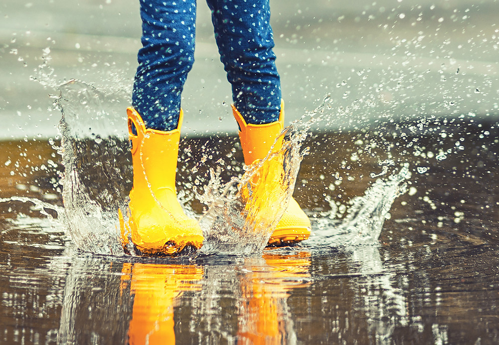 A toddler in yellow rain-boots jumping in a puddle causing a big splash