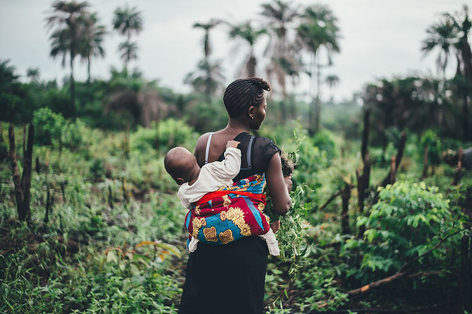 This is a picture of an african woman carrying her baby in a field and walking through a field or farmyard. This is on The Egyptian Doula's page on Birth Doulas and Birth Doula Packages. On the picture are The Egyptian Doulas (Yasmin Aly) listed vision of her vision of a good birth.