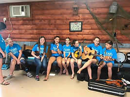 Group of campers sitting around playing their instruments